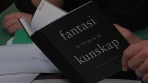 En anteckningsbok med texten fantasi är viktigare än kunskap, på pärmen.
