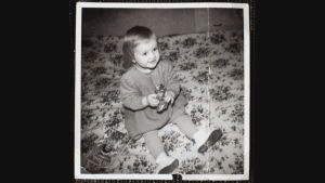 Svarvitt fotografi, liten flicka sitter på golvet