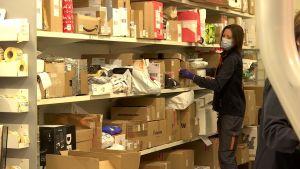 En kvinna sorterar paket. Hyllorna är fulla av paket.