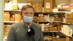 En man med munskydd på står framför hyllor fyllda med paket.