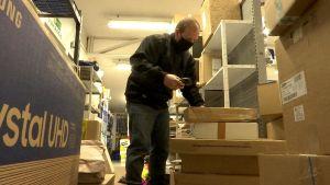 En man står och sorterar paket.