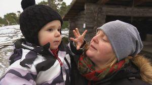 En kvinna med ett barn i famnen. Barnet håller upp fem fingrar.