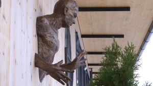en metallstaty föreställande en man som går genom en trävägg