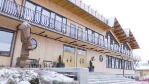 En stor träbyggnad med balkonger längs väggen, fotad utifrån.