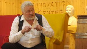 En man med vit skjorta och läderväst sitter i en stor fotölj