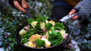 Mat i en stekpanna som står i mossa i skogen. En person håller i stekpannan med ena handen och en slev full med mat med den andra.
