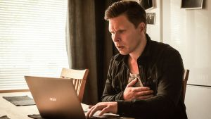 Jarkko (Eero Milonoff) pitelee rintaansa ja lukee huolestuneen näköisenä tekstiä tietokoneen näytöltä keittiössä.
