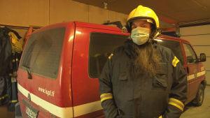 En man framför en brandkårsbil.