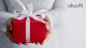 Punainen lahjapaketti, jossa valkoinen nauha, on naisen käsissä.