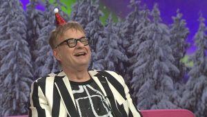Muusikko Iiro Rantala Puoli seitsemän -ohjelman studiossa iloisena jouluhattu päässään.