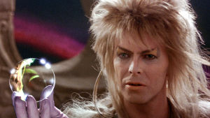 David Bowie peikkokuningas Jarethin roolissa lähikuvassa, lasipallo kädessä.