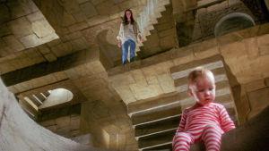 Vauva istuu mielikuvituksellisessa labyrintissä, taustalla nuori tyttö. Kuva elokuvasta Labyrintti.