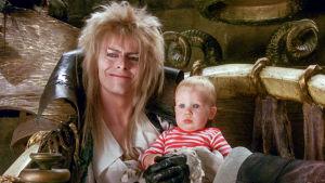 Peikkokuningas Jareth vauva sylissään. Kuva elokuvasta Labyrintti.