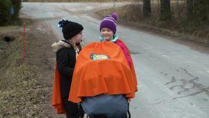Två flickor går längs en landsväg med en barnvagn.