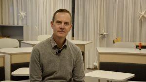 Mikael Fröjdö sitter på en stol i en modern lärmiljö med bord som är ordnade som en hästsko i rummet.