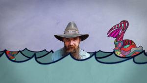 Blaze Foley cowboy-hattu päässä merilavasteessa. Kuva dokumenttielokuvasta.