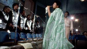 Aretha Franklin laulaa kirkossa, kuoro säestää. Kuva dokumentista Amazing Grace (1972).