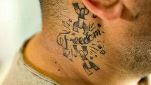 Kaulaan tatuoitu mustalla sana freedom.