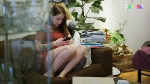 En kvinna sitter i en fatölj och kollar ner på sin telefonskärm.