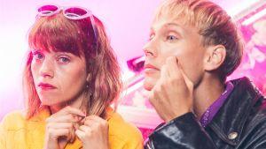 Oona (Anna Airola) ja Arttu (Elias Salonen) vierekkäin lähikuvassa pinkkiä taustaa vasten.