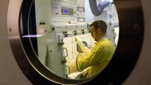 Näkymä lasin takaa erikoissuojattuun laboratorioon, jossa käsitellään ruttobakteereita