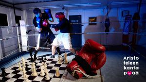 Etualalla shakkilauta, jolla keskeneräinen peli ja punainen nyrkkeilyhanska. Taustalla nyrkkeilykehä, jossa ottelu meneillään.