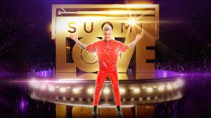 Antti Tuisku seisoo kokokuvassa, punaisessa asussaan, SuomiLOVE-logon edessä