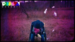 Nainen istuu tuolilla keskellä peltoa pää painettuna polviin. Ympärillä lentelee paperia, hiukset ovat pinkit.