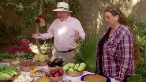 Toimittaja John Sergeant ja arkeologi Suzanne Onstine pöydän ääressä. Pöydällä valikoima herkkuja, joita Egyptin faaraot aikoinaan söivät: munakoisoja, kurpitsoita, sipuleita, kurkkuja, hunajakakkua...