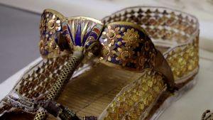 Faarao Tutankhamonin haudasta peräisin oleva kullalla ja emalitöillä runsaasti koristeltu sandaali.