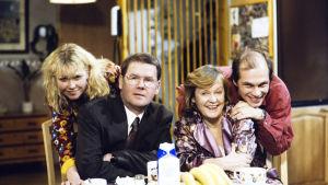 Syrjäntaan perhe: Ulla (Outi Mäenpää), isä Pekka  (Antti Litja),anoppi (Vieno Saaristo) ja Mika (Jari Salmi).