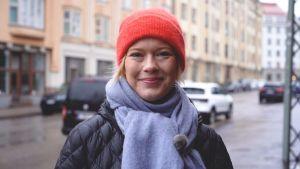 Ekonomen Heidi Schauman står ute på en regnig gata i Tölö i Helsingfors, ler och tittar in i kameran.