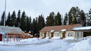 Skolgård täckt i snö. På bilden ett gammalt trähus som är beigemålat, framför liten lekpark med klätterställning och gungor.
