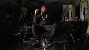 Dontario Hundon poserar i svart läderstol.