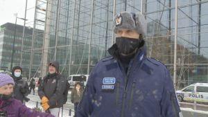 Polis med vinterkläder och svart munskydd.
