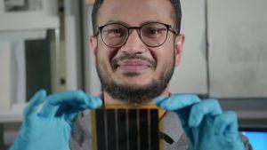 Tutkija Syed Ghufran Hashmi tarkastelee käsissään olevaa perovskiitti-aurinkokennoa.