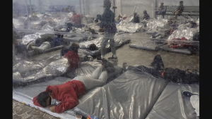 Minderåriga migranter ligger på plastmadrasser på ett stengolv