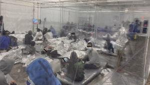 Minderåriga migranter sitter och liggger på tätt packade madrasser i ett amssivt tält. Tältet har delats in i rum med hjälp av plastskynken