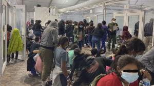Tiotals migranter köar i ett trångt utrymme