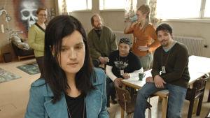 Emma-Liisa Saario (Vilma Melasniemi) ja vastaanottokeskuksen henkilökuntaa sarjassa Poikkeustila