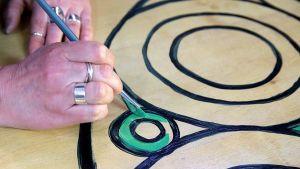 Käsi piirtää ympyröytä.