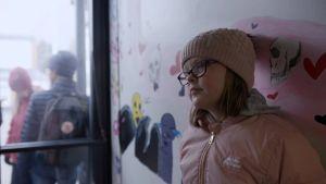 tyttö nojaa seinään koulussa