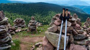 Kävelysauvat nojaavat kiviin vaellusmaisemassa.