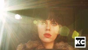 Lähikuva tummahiuksisen naisen kasvoista, jolla on päällään turkis. Valo tulee vasemmalta.