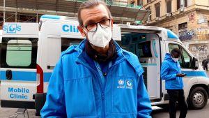 En man står framför en vit skåpbil med texten rörlig klinik.