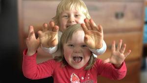 Två småbarn med ljust hår ler och visar sina händer åt kameran.