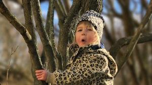 En tjej med mössa grimaserar framför ett träd.