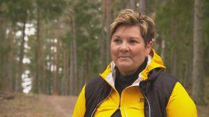 Petra Mannström, en dam med kort hår och gul jacka, står i en skog.