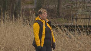 Petra Mannström, en dam med kort hår och gul jacka, står i en vassrugg och tittar ut över havet.