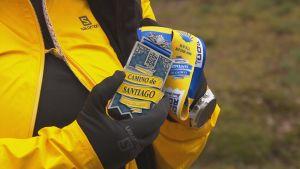 En dam med gulsvart jacka och svarta handskar håller i en kvadratisk medalj med blågult band. På medaljen står Conqueror Camino de Santiago, och ett ett tecken på att vandraren gått pilgrimsleden virtuellt.